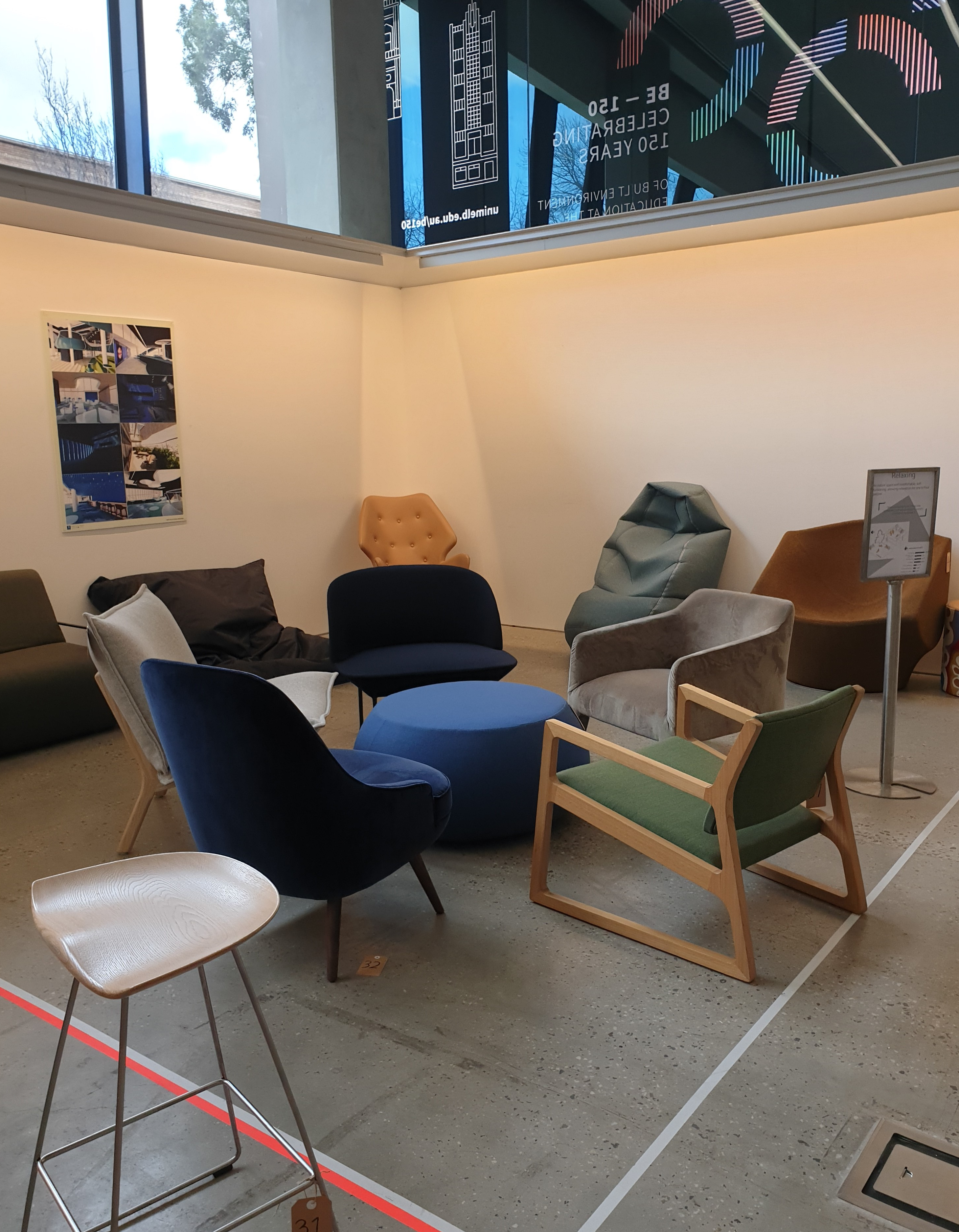 A series of comfortable chairs, set up in a gallery space. The sun is beaming down on a navy blue, velvet chair