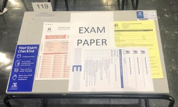 Example of a desk with exam paper, multiple choice answer sheet and script books