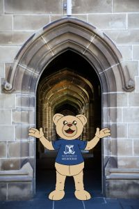 An illustration of the Unimelb mascot Barry standing in front of the Old Quad entrance for phone background