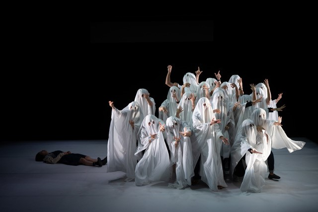 A Greek chorus of ghosts in white sheets, striking poses in front of a body lying on the ground