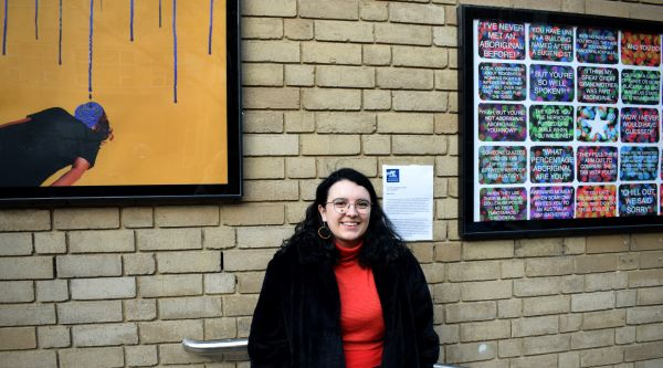 Pierra Van Sparkes in front of her artworks, 'Don't Hold a Drop of Water' (2018) and 'Blackfulla Bingo' (2018), on display at the Outdoor Gallery