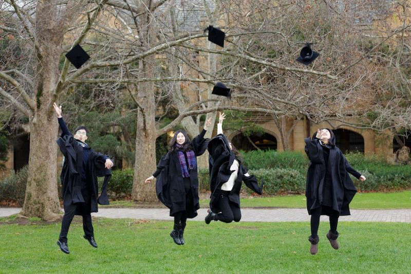 Outside on south lawn, four students celebrate by throwing mortarboard hats into the air.