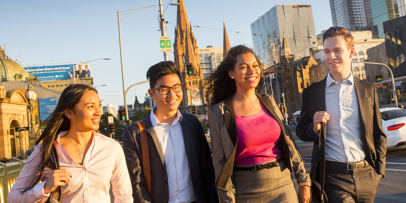 Four professionally dressed students walking through the city.