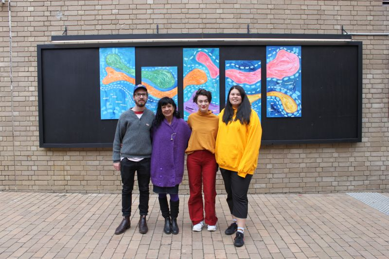 Four artists stand in front of India Money's work